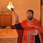 Настоятель сербского прихода протоиерей Радован окропляет св. водой стены храма